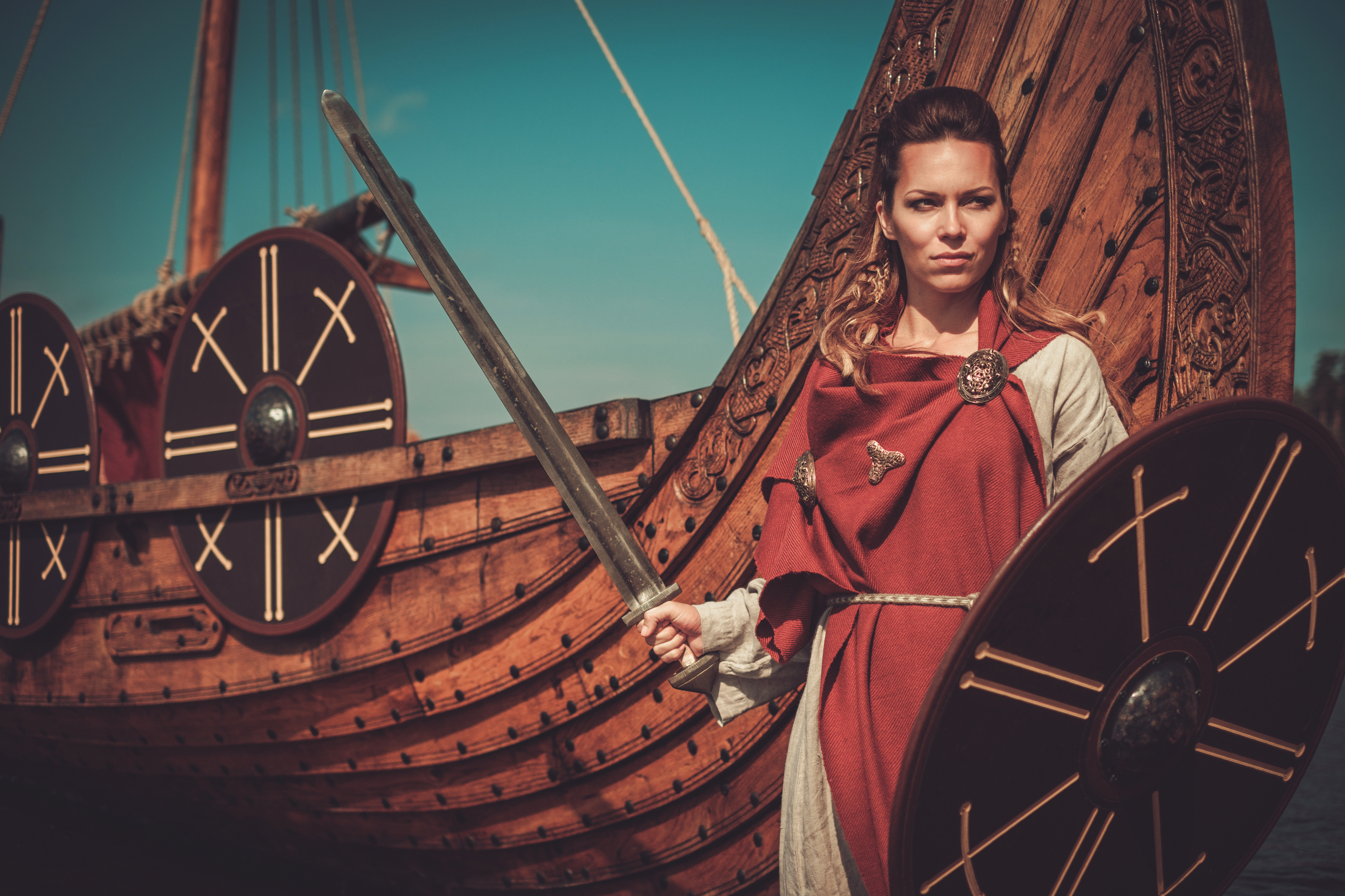 Viking woman in traditional clothes near drakkar.